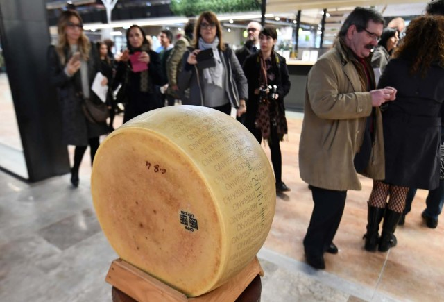 People walk past a loaf of parmesan cheese on display at a stand during a press tour at FICO Eataly World agri-food park in Bologna on November 9, 2017. FICO Eataly World, said to be the world's biggest agri-food park, will open to the public on November 15, 2017. The free entry park, widely described as the Disney World of Italian food, is ten hectares big and will enshrine all the Italian food biodiversity. / AFP PHOTO / Vincenzo PINTO