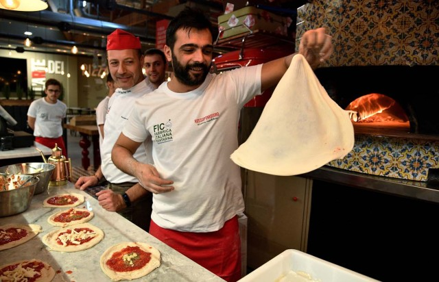 Pizza bakers prepare traditional pizza margherita during a press tour at FICO Eataly World agri-food park in Bologna on November 9, 2017. FICO Eataly World, said to be the world's biggest agri-food park, will open to the public on November 15, 2017. The free entry park, widely described as the Disney World of Italian food, is ten hectares big and will enshrine all the Italian food biodiversity. / AFP PHOTO / Vincenzo PINTO