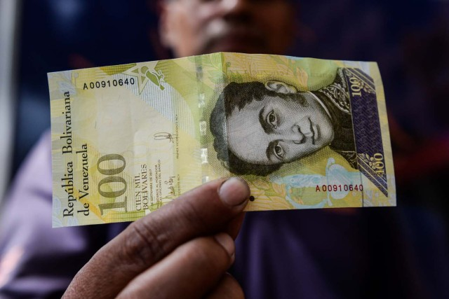 A man shows a new one hundred thousand-Bolivar-note in Caracas on November 9, 2017. The new bill is worth 29,89 US dollars in the official market and 2 dollars in the black market at November 9, 2017 exchange rate. / AFP PHOTO / FEDERICO PARRA