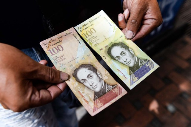 A man holds the new one hundred thousand-Bolivar-note (R) comparing it to the one hundred note, to show the resemblance between both bills in Caracas on November 9, 2017. The new bill is worth 29,89 US dollars in the official market and 2 dollars in the black market at November 9, 2017 exchange rate. / AFP PHOTO / FEDERICO PARRA