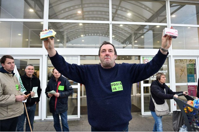 French farmer Ghislain De Viron (C) presents butter made from a blend of European Union milk as a substitute for French butter in front of the hyper market Leclerc d'Alllonnes, near Le Mans, northwestern France, on November 10, 2017 during an action to sell butter at a price that will remunerate them. / AFP PHOTO / JEAN-FRANCOIS MONIER