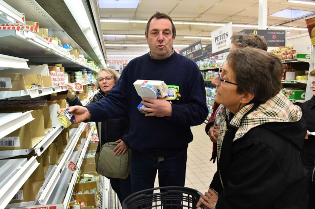 French farmer Ghislain De Viron (C) holds butter made from a blend of European Union milk as a substitute for French butter as he speaks to consummers in the hyper market Leclerc d'Alllonnes, near Le Mans, northwestern France, on November 10, 2017 during an action of French farmers to sell butter at a price that will remunerate them. / AFP PHOTO / JEAN-FRANCOIS MONIER