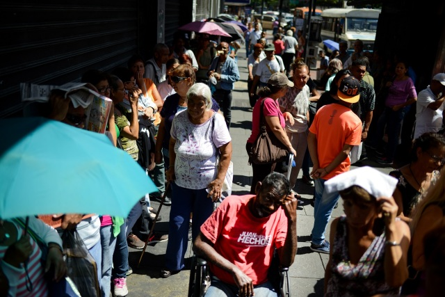 People queue outside a supermarket in Caracas to buy basic foodstuffs and household products on November 10, 2017. In crisis-stricken Venezuela, the cost of the basic basket of goods soared to nearly 2.7 million bolivars in September, the equivalent of six minimum monthly wages. / AFP PHOTO / FEDERICO PARRA