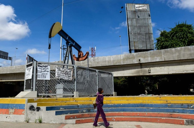 """A woman walks by a small square with an oil pump in one of the access roads to the Central University of Venezuela, in Caracas on November 14, 2017. Venezuela has been declared in """"selective default"""" by Standard and Poor's after failing to make interest payments on bond issues as it tries to refinance its $150 billion foreign debt. / AFP PHOTO / Federico PARRA"""