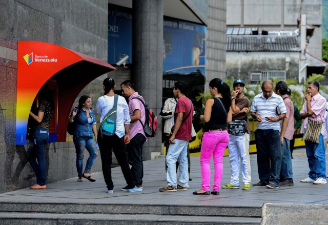 "People queue to withdraw money from an ATM in Caracas on November 14, 2017. Venezuela has been declared in ""selective default"" by Standard and Poor's after failing to make interest payments on bond issues as it tries to refinance its $150 billion foreign debt. / AFP PHOTO / Federico PARRA"