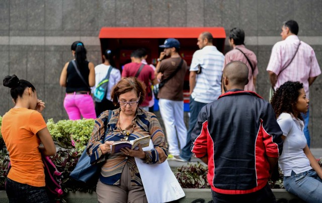 "A woman reads as she queues to withdraw money from an ATM in Caracas on November 14, 2017. Venezuela has been declared in ""selective default"" by Standard and Poor's after failing to make interest payments on bond issues as it tries to refinance its $150 billion foreign debt. / AFP PHOTO / Federico PARRA"