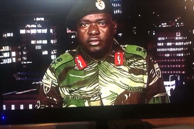 """This screen grab taken early on November 15, 2017 from a television broadcast on the Zimbabwe Broadcasting corporation (ZBC) shows Zimbabwe Major General Sibusiso Moyo reading a statement at the ZBC broadcast studio in Harare. Zimbabwe's military appeared to be in control of the country on November 15 as generals denied staging a coup but used state television to vow to target """"criminals"""" close to President Robert Mugabe. / AFP PHOTO / -"""