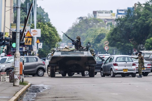 """An armoured personnel carrier stations by an intersection as Zimbabwean soldiers regulate traffic in Harare on November 15, 2017. Zimbabwe's military appeared to be in control of the country on November 15 as generals denied staging a coup but used state television to vow to target """"criminals"""" close to President Mugabe. / AFP PHOTO / -"""