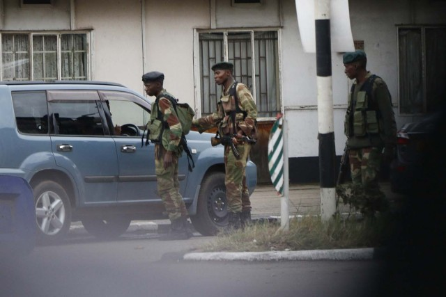 """Zimbabwean soldiers control vehicles as they stand by an intersection as they regulate civilian traffic in Harare on November 15, 2017. Zimbabwe's military appeared to be in control of the country on November 15 as generals denied staging a coup but used state television to vow to target """"criminals"""" close to President Mugabe. / AFP PHOTO / -"""