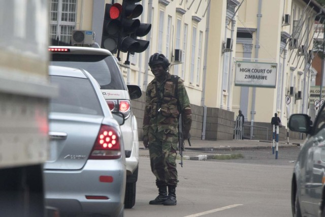 """Zimbabwean soldiers stand by an intersection as they regulate civilian traffic in front of the High Court of Zimbabwe in Harare on November 15, 2017. Zimbabwe's military appeared to be in control of the country on November 15 as generals denied staging a coup but used state television to vow to target """"criminals"""" close to President Mugabe. / AFP PHOTO / -"""