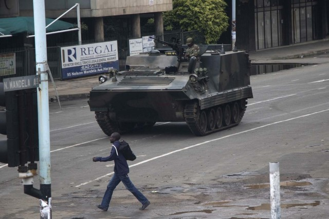 """Zimbabwean soldiers stand by an intersection as they regulate civilian traffic in Harare on November 15, 2017. Zimbabwe's military appeared to be in control of the country on November 15 as generals denied staging a coup but used state television to vow to target """"criminals"""" close to President Mugabe. / AFP PHOTO / -"""
