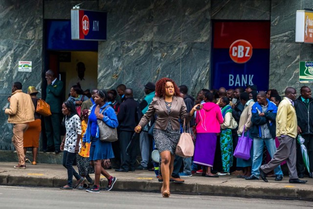 """A woman passes the street as Harare residents queue outside a bank in Harare on November 15, 2017. Zimbabwe's military appeared to be in control of the country on November 15 as generals denied staging a coup but used state television to vow to target """"criminals"""" close to President Mugabe. / AFP PHOTO / -"""
