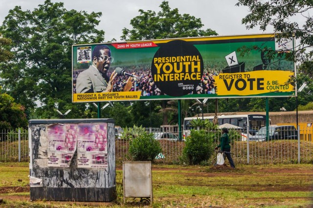 """A woman in military uniform walks past a billboard with a poster of ruling party Zimbabwe African National Union - Patriotic Front (Zanu PF) and a picture of President Robert Mugabe in Harare on November 15, 2017. Zimbabwe's military appeared to be in control of the country on November 15 as generals denied staging a coup but used state television to vow to target """"criminals"""" close to President Mugabe. / AFP PHOTO / -"""