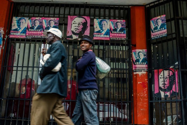 """Harare residents walk past campaign posters portraying Zimbabwe Opposition and Movement for Democratic Change leader Morgan Tsvangirai in Harare on November 15, 2017. Zimbabwe's military appeared to be in control of the country on November 15 as generals denied staging a coup but used state television to vow to target """"criminals"""" close to President Mugabe. / AFP PHOTO / -"""