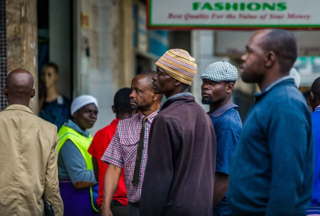 """Residents queue outside a bank in Harare on November 15, 2017. Zimbabwe's military appeared to be in control of the country on November 15 as generals denied staging a coup but used state television to vow to target """"criminals"""" close to President Mugabe. / AFP PHOTO / -"""