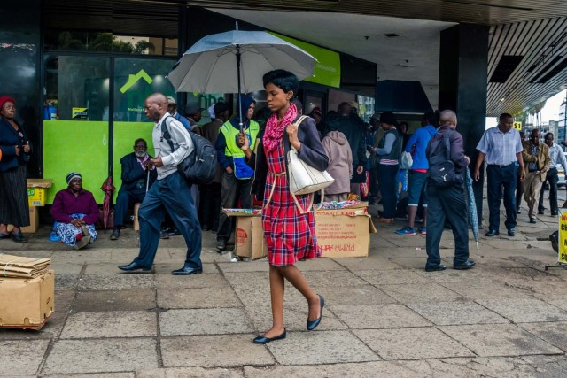 """A woman with an umbrella walks past residents queuing outside a bank in Harare on November 15, 2017. Zimbabwe's military appeared to be in control of the country on November 15 as generals denied staging a coup but used state television to vow to target """"criminals"""" close to President Mugabe. / AFP PHOTO / -"""