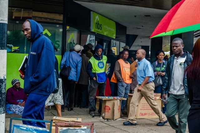 """Residents walk in a street as others queue outside a bank in Harare on November 15, 2017. Zimbabwe's military appeared to be in control of the country on November 15 as generals denied staging a coup but used state television to vow to target """"criminals"""" close to President Mugabe. / AFP PHOTO / -"""