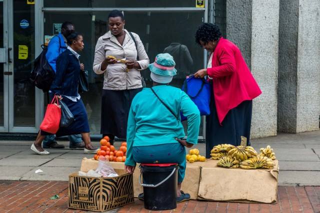 """Residents buy fruits from a street vendor in Harare on November 15, 2017. Zimbabwe's military appeared to be in control of the country on November 15 as generals denied staging a coup but used state television to vow to target """"criminals"""" close to President Mugabe. / AFP PHOTO / -"""