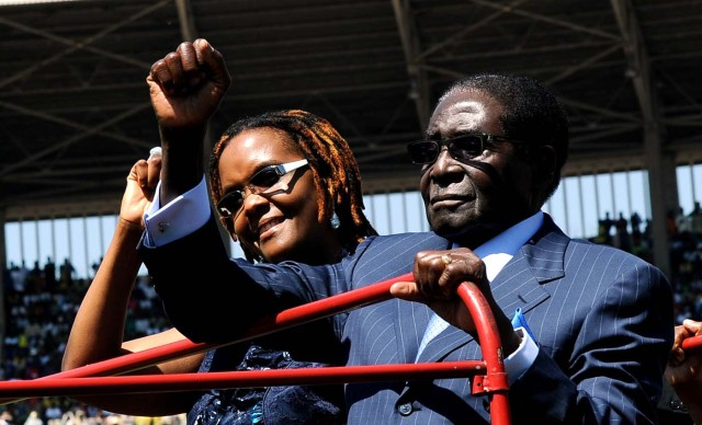 "(FILES) This file photo taken on August 22, 2013 shows Zimbabwean President Robert Mugabe (R), accompanied by wife Grace, raising his fist as he greets the crowd at his inauguration ceremony in Harare at the National 60,000-seat sports stadium. Zimbabwe's military appeared to be in control of the country on November 15, 2017 as generals denied staging a coup but used state television to vow to target ""criminals"" close to President Robert Mugabe. Mnangagwa's dismissal left Mugabe's wife Grace, 52, in prime position to succeed her husband as the next president -- a succession strongly opposed by senior ranks in the military. / AFP PHOTO / ALEXANDER JOE"