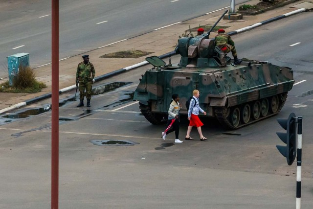 """Young women walk past an armoured personnel carrier that stations by an intersection as Zimbabwean soldiers regulate traffic in Harare on November 15, 2017. Zimbabwe's military appeared to be in control of the country on November 15 as generals denied staging a coup but used state television to vow to target """"criminals"""" close to President Mugabe. / AFP PHOTO / -"""