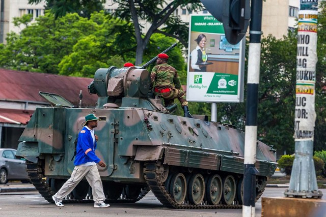 """A man walks past an armoured personnel carrier that stations by an intersection as Zimbabwean soldiers regulate traffic in Harare on November 15, 2017. Zimbabwe's military appeared to be in control of the country on November 15 as generals denied staging a coup but used state television to vow to target """"criminals"""" close to President Mugabe. / AFP PHOTO / -"""
