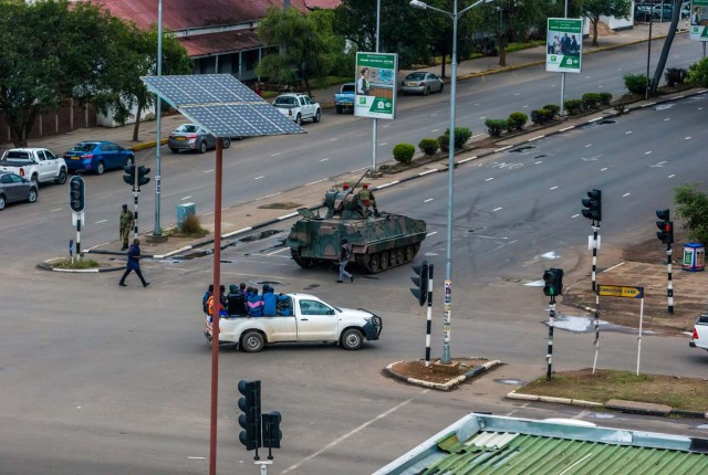 """An armoured personnel carrier stations at an intersection as Zimbabwean soldiers regulate traffic in Harare on November 15, 2017. Zimbabwe's military appeared to be in control of the country on November 15 as generals denied staging a coup but used state television to vow to target """"criminals"""" close to President Mugabe. / AFP PHOTO / -"""