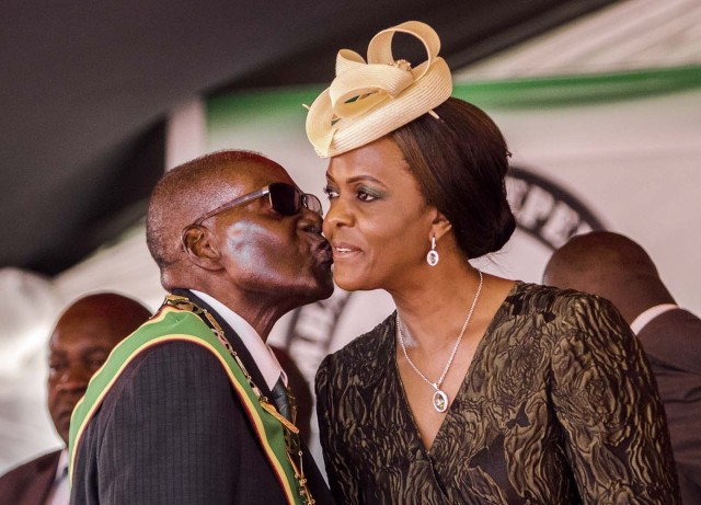 "(FILES) This file photo taken on April 18, 2017 shows President Robert Mugabe kissing his wife and first lady Grace Mugabe during during the country's 37th Independence Day celebrations at the National Sports Stadium in Harare. Zimbabwe's military appeared to be in control of the country on November 15, 2017 as generals denied staging a coup but used state television to vow to target ""criminals"" close to President Robert Mugabe. Mnangagwa's dismissal left Mugabe's wife Grace, 52, in prime position to succeed her husband as the next president -- a succession strongly opposed by senior ranks in the military. / AFP PHOTO / Jekesai NJIKIZANA"
