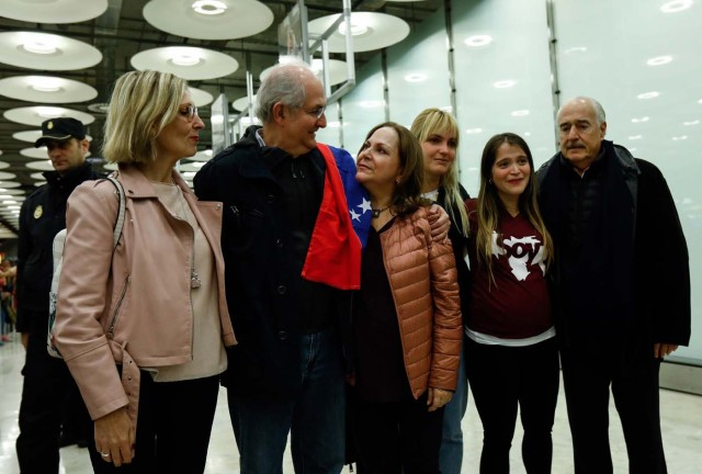 The mayor of Caracas, Antonio Ledezma (2-L) is greet by family members upon his arrival to the Barajas Airport on November 18, 2017 in Madrid. Ledezma arrived from Bogota to Spain on November 18 after escaping house arrest in the Venezuelan capital, after having been accused of conspiracy against the government of Nicolas Maduro. / AFP PHOTO / OSCAR DEL POZO