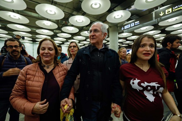 The mayor of Caracas, Antonio Ledezma (C) is greeted by his wife Mitzy Capriles (2-L) and his daughter Antoneta (R) upon his arrival to the Barajas Airport on November 18, 2017 in Madrid. Ledezma arrived from Bogota to Spain on November 18 after escaping house arrest in the Venezuelan capital, after having been accused of conspiracy against the government of Nicolas Maduro. / AFP PHOTO / OSCAR DEL POZO
