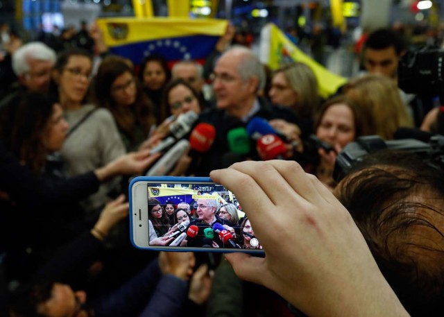 A journalist captures images of the mayor of Caracas, Antonio Ledezma (C) as he speaks to journalists upon his arrival to the Barajas Airport on November 18, 2017 in Madrid. Ledezma arrived from Bogota to Spain on November 18 after escaping house arrest in the Venezuelan capital, after having been accused of conspiracy against the government of Nicolas Maduro. / AFP PHOTO / OSCAR DEL POZO