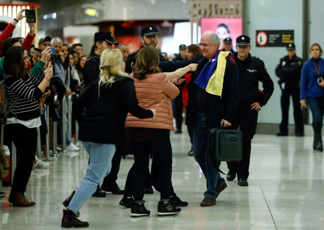 The mayor of Caracas, Antonio Ledezma (C) is greet by family members upon his arrival to the Barajas Airport on November 18, 2017 in Madrid. Ledezma arrived from Bogota to Spain on November 18 after escaping house arrest in the Venezuelan capital, after having been accused of conspiracy against the government of Nicolas Maduro. / AFP PHOTO / OSCAR DEL POZO