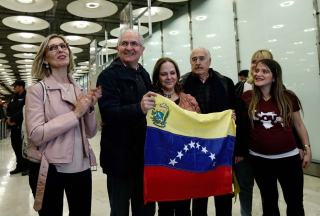 The mayor of Caracas, Antonio Ledezma (2-L) poses with family members upon his arrival to the Barajas Airport on November 18, 2017 in Madrid. Ledezma arrived from Bogota to Spain on November 18 after escaping house arrest in the Venezuelan capital, after having been accused of conspiracy against the government of Nicolas Maduro. / AFP PHOTO / OSCAR DEL POZO