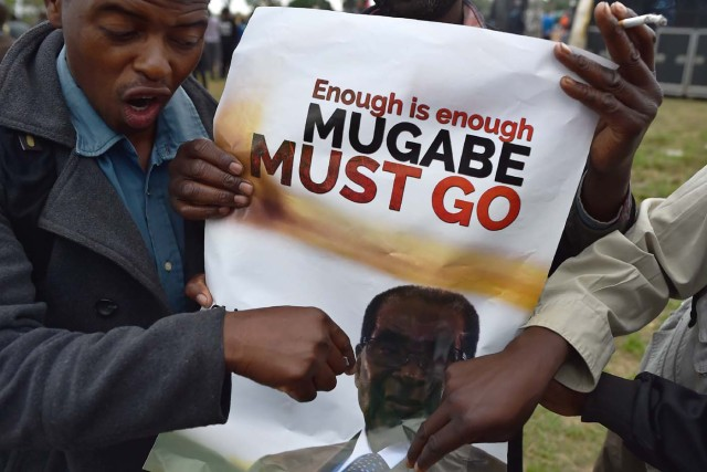 A man gestures towards a banner during a demonstration demanding the resignation of Zimbabwe's president on November 18, 2017 in Harare. Zimbabwe was set for more political turmoil November 18 with protests planned as veterans of the independence war, activists and ruling party leaders called publicly for President Robert Mugabe to be forced from office. / AFP PHOTO / -