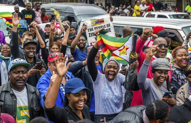People shout slogans and wave Zimbabwean national flags during a demonstration demanding the resignation of Zimbabwe's president on November 18, 2017 in Harare. Zimbabwe was set for more political turmoil November 18 with protests planned as veterans of the independence war, activists and ruling party leaders called publicly for President Robert Mugabe to be forced from office. / AFP PHOTO / Jekesai NJIKIZANA