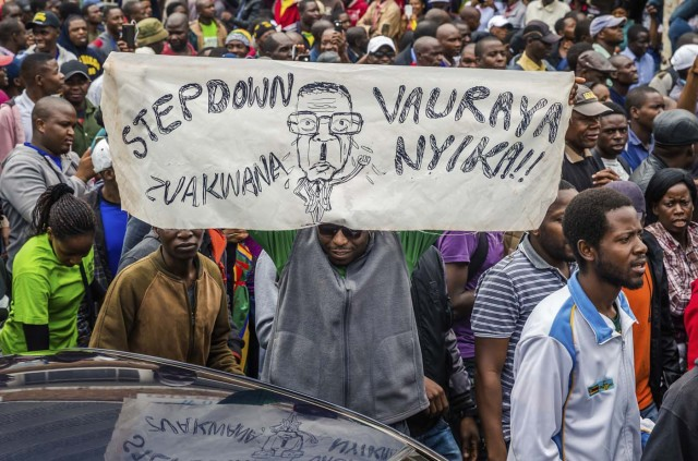 People carry placards during a demonstration demanding the resignation of Zimbabwe's president on November 18, 2017 in Harare. Zimbabwe was set for more political turmoil November 18 with protests planned as veterans of the independence war, activists and ruling party leaders called publicly for President Robert Mugabe to be forced from office. / AFP PHOTO / Jekesai NJIKIZANA