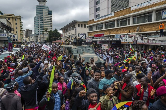 People cheer a passing Zimbabwe Defense Force military vehicle during a demonstration demanding the resignation of Zimbabwe's president on November 18, 2017 in Harare. Zimbabwe was set for more political turmoil November 18 with protests planned as veterans of the independence war, activists and ruling party leaders called publicly for President Robert Mugabe to be forced from office. / AFP PHOTO / Jekesai NJIKIZANA