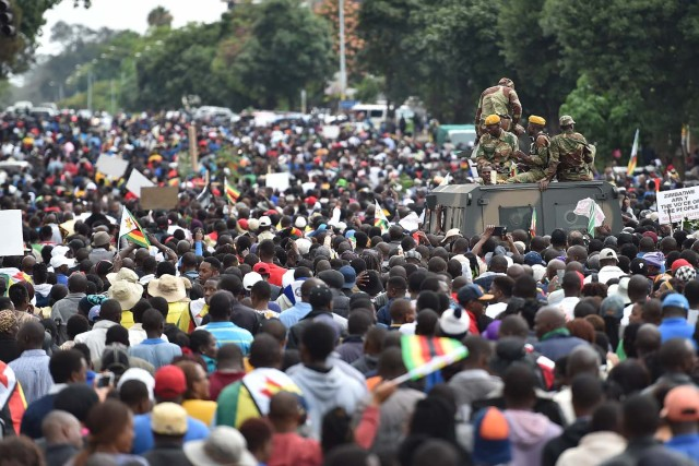 People march past an armoured personnel carrier towards the State House during a demonstration demanding the resignation of Zimbabwe's president on November 18, 2017 in Harare. Zimbabwe was set for more political turmoil November 18 with protests planned as veterans of the independence war, activists and ruling party leaders called publicly for President Robert Mugabe to be forced from office. / AFP PHOTO / -