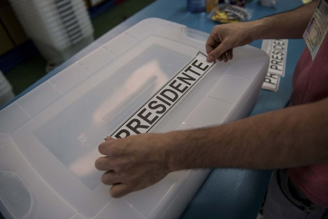 """A man places a sticker reading """"President"""" on a ballot box as polling stations are being set up at the National Stadium in Santiago on November 18, 2017 on the eve of Chile's general elections. After four years of socialist rule, Chile is expected to revert to the right in elections Sunday, with Sebastian Pinera set to return as president, confirming a shift to conservative leaders across Latin America. Opinion polls make Pinera, a 67-year-old billionaire businessman sometimes referred to as """"Chile's Berlusconi"""", the hot favourite to return to the presidency he occupied from 2010-2014.  / AFP PHOTO / Martin BERNETTI"""