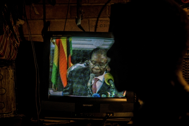 A man looks at a television set broadcasting a state address by Zimbabwe's President Robert Mugabe in Mbare, Harare on November 19, 2017.  Zimbabwean President Robert Mugabe, in a much-expected TV address, stressed he was still in power after his authoritarian 37-year reign was rocked by a military takeover. Many Zimbabweans expected Mugabe to resign after the army seized power last week. But Mugabe delivered his speech alongside the uniformed generals who were behind the military intervention. In his address, Mugabe made no reference to the clamour for him to resign. / AFP PHOTO / ZINYANGE AUNTONY