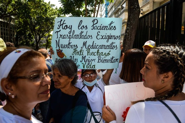 A woman holds a sign during an anti-government demonstration protesting for the shortage of medicines in Caracas on November 20, 2017. / AFP PHOTO / FEDERICO PARRA