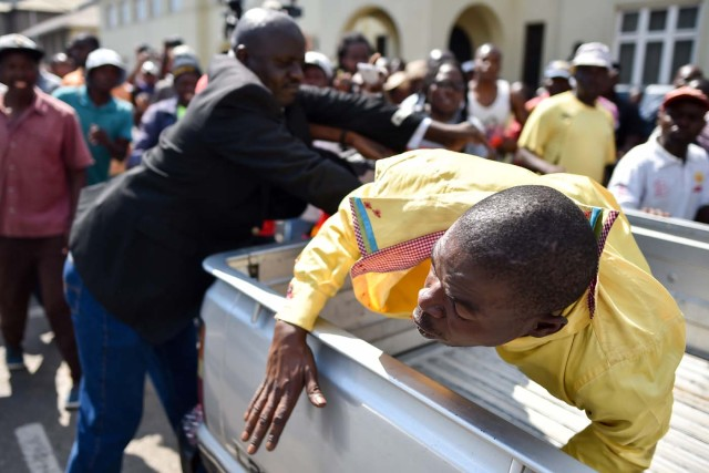 A man accused of supporting Zimbabwe President is thrown into the back of a pick up truck on November 21, 2017 outside parliament, as Parliament prepares to start impeachment proceedings against the President, while ousted vice president who could be the country's next leader, tells him to step down. As the 93-year-old autocrat faced intensifying pressure to quit, southern Africa's regional bloc announced it was dispatching the presidents of Angola and South Africa to Harare to discuss the crisis. / AFP PHOTO / TONY KARUMBA