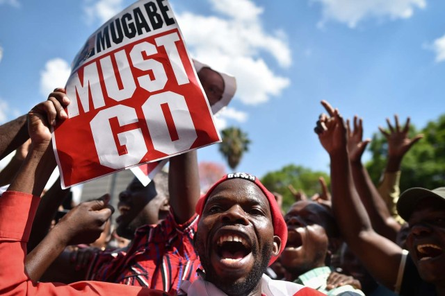An anti-Zimbabwe President holds a placard during a gathering at Unity square, on November 21, 2017 in the capital Harare, praying and asking for Mugabe's impeachment, as Parliament prepares to start impeachment proceedings against the President, while ousted vice president who could be the country's next leader, tells him to step down. As the 93-year-old autocrat faced intensifying pressure to quit, southern Africa's regional bloc announced it was dispatching the presidents of Angola and South Africa to Harare to discuss the crisis. / AFP PHOTO / TONY KARUMBA