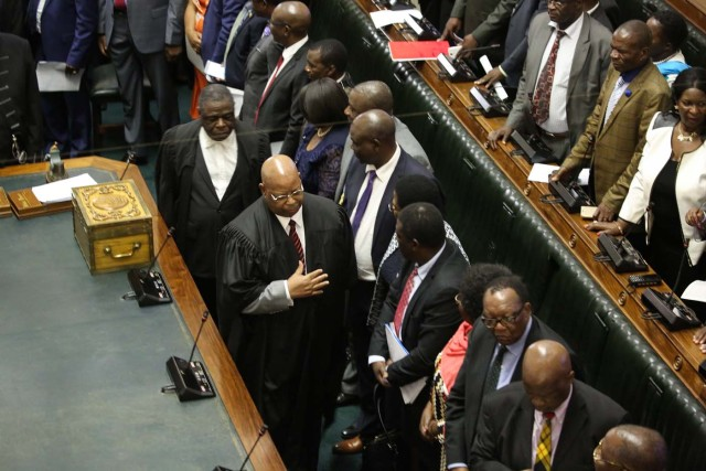 Speaker of the National Assembly Jacob Mudenda (C with black robe) enters the chamber as Zimbabwean Members of Parliament assemble for a parliamentary session where a motion is moved to impeach Zimbabwe President on November 21, 2017 at the Zimbabwean Parliament in Harare. Parliament prepares to start impeachment proceedings against the President, while ousted vice president who could be the country's next leader, tells him to step down. As the 93-year-old autocrat faced intensifying pressure to quit, southern Africa's regional bloc announced it was dispatching the presidents of Angola and South Africa to Harare to discuss the crisis. / AFP PHOTO / POOL / AARON UFUMELI