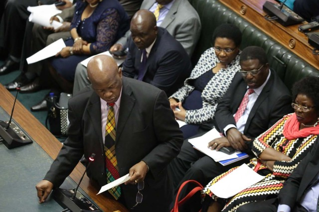 Member of Parliament Patrick Chinamasa (L) moves forward a motion to impeach Zimbabwe President during a parliamentary session on November 21, 2017 at the Zimbabwean Parliament in Harare. Parliament prepares to start impeachment proceedings against the President, while ousted vice president who could be the country's next leader, tells him to step down. As the 93-year-old autocrat faced intensifying pressure to quit, southern Africa's regional bloc announced it was dispatching the presidents of Angola and South Africa to Harare to discuss the crisis. / AFP PHOTO / POOL / AARON UFUMELI
