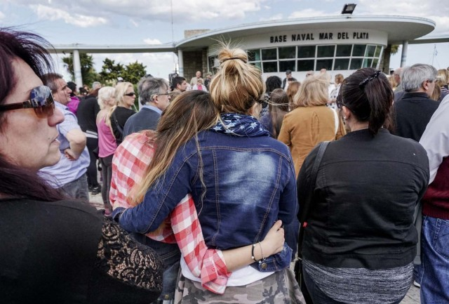 People pray outside Argentina's Navy base in Mar del Plata, on the Atlantic coast south of Buenos Aires, on Novembe 22, 2017, while the search for the missing ARA San Juan submarine keeps going on. The clock ticked down Wednesday on hopes of finding alive the 44 crew members of an Argentine submarine missing for a week despite a massive search of surface and seabed, amid fears their oxygen had run out. The ARA San Juan would have had enough oxygen for its crew to survive underwater in the South Atlantic for seven days since its last contact, according to officials. / AFP PHOTO / EITAN ABRAMOVICH