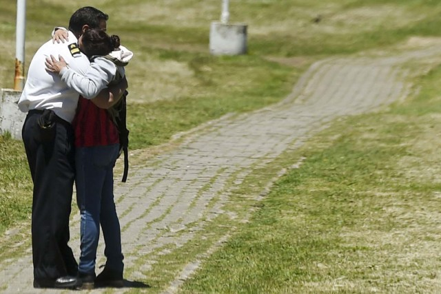 "A relative and a comrade of one of the 44 crew members of Argentine missing submarine, embrace each other in grief at Argentina's Navy base in Mar del Plata, on the Atlantic coast south of Buenos Aires, on November 23, 2017. An unusual noise heard in the ocean near the last known position of the San Juan submarine was ""consistent with an explosion,"" Argentina's navy announced Thursday. ""An anomalous, singular, short, violent and non-nuclear event consistent with an explosion,"" occurred shortly after the last communication of the San Juan and its 44 crew, navy spokesman Captain Enrique Baldi told a news conference in Buenos Aires. / AFP PHOTO / EITAN ABRAMOVICH"
