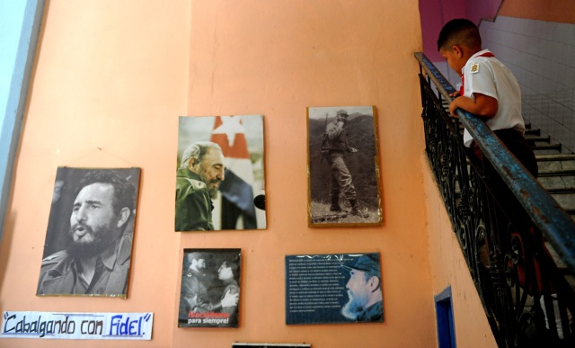 A Cuban primary school student looks at a wall decorated with posters of late Cuban leader Fidel Castro in Havana, on November 23, 2017. Cuba commemorates on November 25 the first anniversary of the death of Fidel Castro, focused on an electoral process that will imply a presidential change, in a framework of economic regression, hostility from the United States, and stagnation in its reforms. / AFP PHOTO / YAMIL LAGE