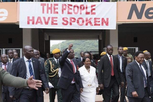 El presidente electo Emmerson Mnangagwa (C, L) gesticula mientras llega con su esposa Auxilia (C, R) en el Estadio Nacional Deportivo en Harare, el 24 de noviembre de 2017 durante la ceremonia de inauguración. El vicepresidente expulsado de Zimbabue prestaría juramento como presidente el 24 de noviembre de 2017, marcando el capítulo final de un drama político que derrocó a su predecesor después de una toma militar. / AFP PHOTO / Marco Longari