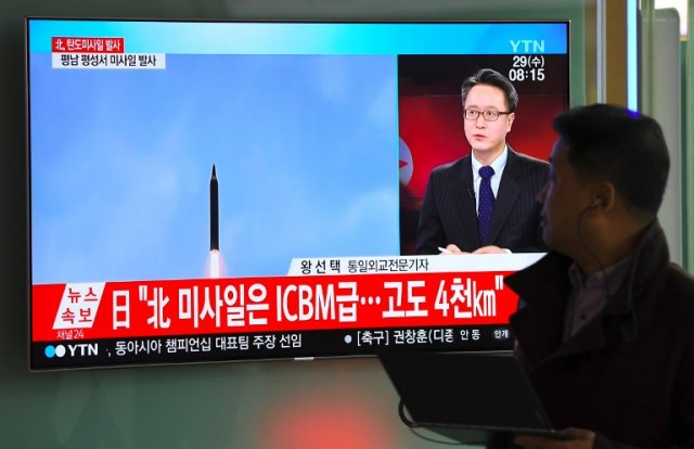 A man walks past a television screen showing a file video footage of North Korea's missile launch, at a railway station in Seoul on November 29, 2017. North Korea test fired what appeared to be an intercontinental ballistic missile on November 29, in a major challenge to US President Donald Trump after he slapped fresh sanctions on Pyongyang and declared it a state sponsor of terrorism. / AFP PHOTO / JUNG Yeon-Je
