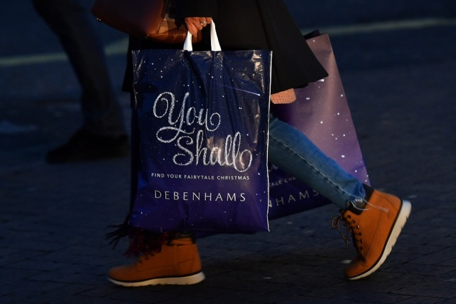 A shopper carries a Christmas-themed bag from the retailer Debenhams as they walk along Oxford Street in London, on November 23, 2017. Black Friday is a sales offer originating from the US where retailers slash prices on the day after the Thanksgiving holiday. In the UK it is used as a marketing device to entice Christmas shoppers with the discounts at stores often lasting for a week. / AFP PHOTO / Ben STANSALL